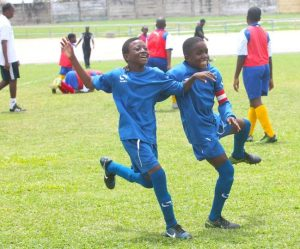 Jaden Nurse (left) scored the all important penalty for Wesley Hall Primary and took time to celebrate with captain Renico Rouse. (Pictures by Morissa Lindsay)