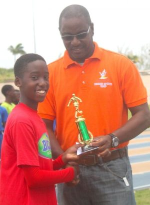 halil Vanderpool-Nurse is all smiles as he receives his trophy for Most Valuable Player in the final from Wayne Robinson of the National Sports Council.