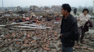 Residents look through the rubble of destroyed houses after a tornado hit Yancheng on Thursday.