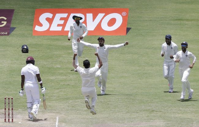 India's bowler Mohammed Shami, back to camera, jumps to celebrates with teammates the dismissal of West Indies' Darren Bravo, left, during day three of their first cricket Test match at the Sir Vivian Richards Stadium in North Sound, Antigua, Saturday, July 23, 2016. (AP Photo/Ricardo Mazalan)