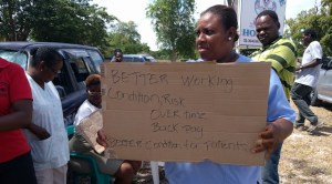 A striking Clarevue Psychiatric Hospital worker holds a placard stating her demands.