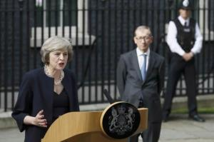 Britain's Prime Minister Theresa May, watched by husband Philip, speaks to the media outside number 10 Downing Street, in central London, Britain on Wednesday.