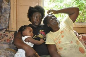 A grief-stricken Cora Eastmond being comforted by her daughter Gaile Eastmond as she holds her deceased daughter Melissa Eastmond's (inset) baby close to her bosom.