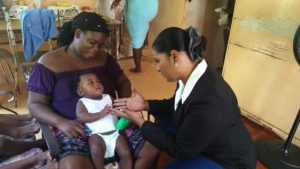 BWA Corporate Communications Specialist Joy-ann Haigh (right) asking baby Jelissa who is being held by her aunt Faye to come to her.