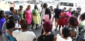 Teachers from Duhaney Park Primary School surround Ruby McKoy, mother of the injured teen, while they pray outside Kingston Public Hospital Thursday.