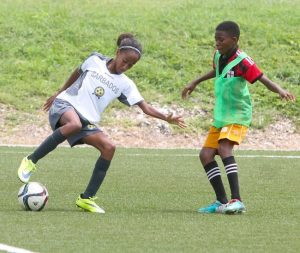 Zara Owen, one of Barbados Under-15 players, cuts this ball away from Tajari Sutherland of the National Sports Council's Under-17 team.