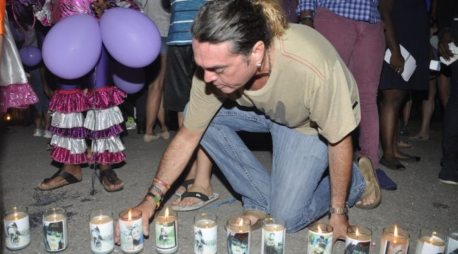 Allan Sheppard placing a candle in memory of his niece Renee Ratcliffe.