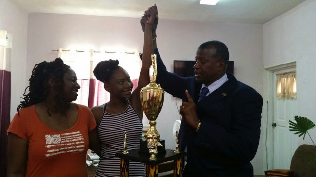 Pastor David Durant of Restoration Ministries Church (right) congratulating the 21-year-old for her achievement as her mother Carol (left) looks on.