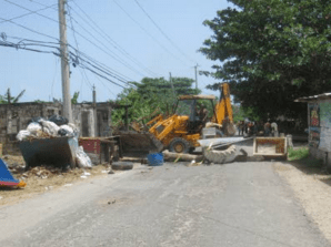 A bulldozer clears a section of the Manchioneal main road.