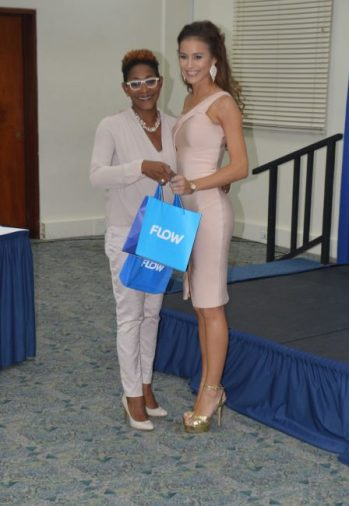 Miss Universe Barbados receiving some of her prizes from FLOW's marketing manager Marilyn Sealy.