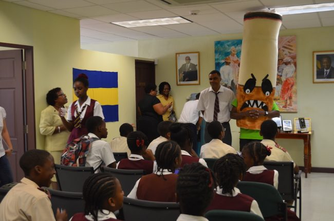 Research and Information Officer Jonathan Yearwood (next to mascot) speaking to students during one of the NCSA's activities.