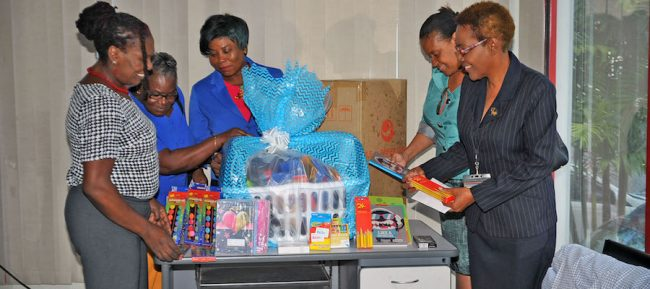 President of the Family Care Support Group, Kedelyn Morgan (left), looking through the school supplies with Senior Clerk in the Office of the Attorney General, Joan Morris, Clerical Officer in the Office of the Attorney General, Sonia Phillips, Administrative Officer and HIV Coordinator in the Ministry of Home Affairs, Frances Scantlebury, and Administrative Officer and HIV Coordinator in the Office of the Attorney General, Cheryl Grogan.