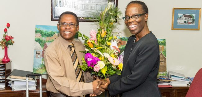 GPO's Margaret Ashby (right) receives flowers from UWI Alumni Association President Philip Chandler.