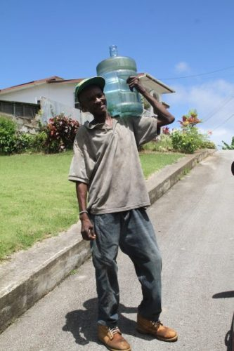 Adrian Parris of Surinam,  St Joseph carrying a gallon of water to a neighbour's house.