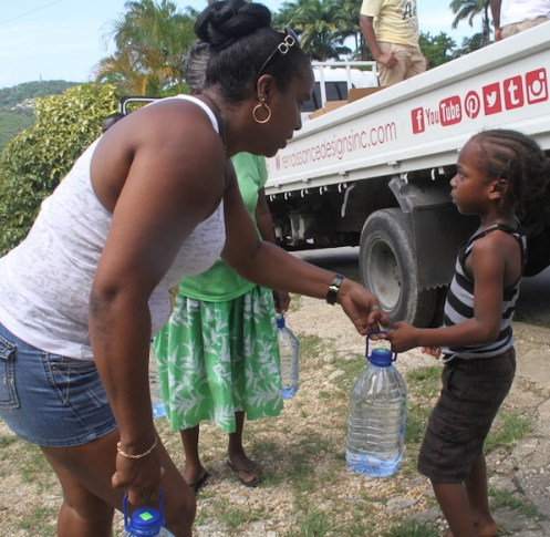 Jennifer Young, Public Relation  Officer of Rennaissance Designs helps a youngster to a bottle of water.