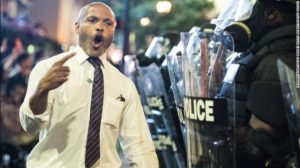 Public defender, Toussaint Romain, inserted himself between the wall of armoured police and the angry crowd.