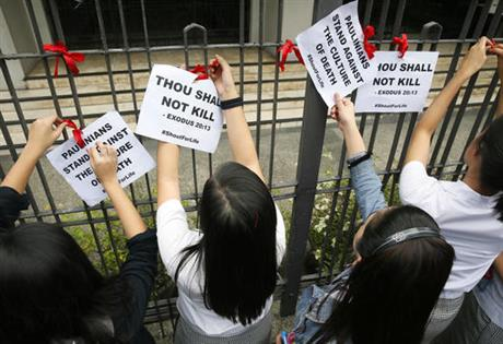 "Students from St Paul's University tie red ribbons as they come out from their campus to protest the killings being perpetrated in the unrelenting ""War on Drugs"" campaign of President Rodrigo Duterte, Friday."