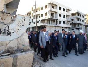 Syrian President Bashar Assad (centre) walks on a street with officials after performing the morning Eid al-Adha prayers in Daraya, a blockaded Damascus suburb, Syria, on Monday.