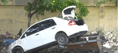 The force of flood water last Friday caused this car's rear end to end up on a garbage skip at the Fisheries Department on Marcus Garvey Drive.