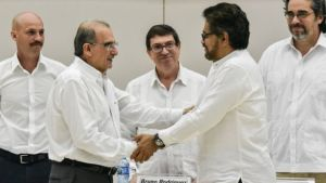 The head of the Colombian government delegation Humberto de la Calle (left) and the head of the FARC-EP delegation Ivan Marquez (right) shake hands after the signing the historic deal.