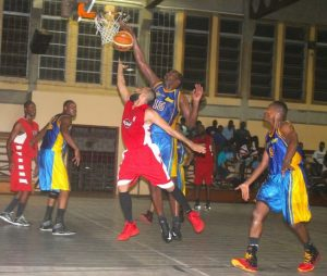 Zahir Motara (No.5 in red) scored a game-high 27 points for  Warrens Sports Club but on this occasion is blocked by Andre Boadu (No.15) of Lakers.