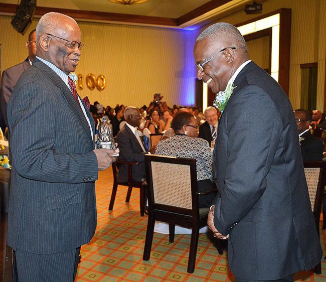 Governor General Sir Elliott Belgrave jokes with Bishop Dr Pat Glasgow before presenting him the Lydia Dowdye-Mings Servanthood Award.
