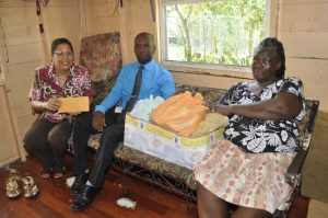 From left, Bonita Morgan and William Warner of the Yes We Care committee of Baobab Tower which presented food and money to Cora Eastmond.