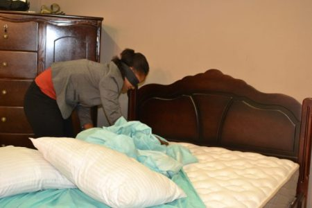 A Courts employee tries making a bed while blindfolded.