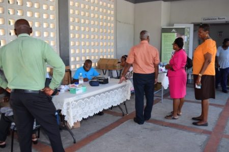 Employees of the Ministry of Education line up at the Barbados Diabetes Association booth.