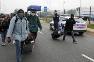 French police stand near as migrants carry their belongings at the start of their evacuation and transfer to reception centers in France, and the dismantlement of the camp called the 'Jungle' in Calais, France.