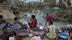 Haitian women and children gather in Port Salut to wash clothes after the devastating effects of Matthew.