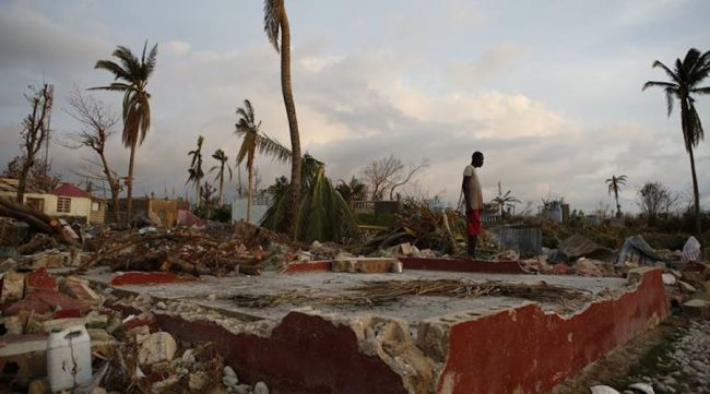 A young man stands next to the foundation of his former house, in a seaside fishing neighborhood almost completely destroyed by Hurricane Matthew in Port Salut, Haiti, Sunday, Oct. 9, 2016. Nearly a week after the storm smashed into southwestern Haiti, some communities along the southern coast have yet to receive any assistance, leaving residents who have lost their homes and virtually all of their belongings struggling to find shelter and potable water.(AP Photo/Rebecca Blackwell)