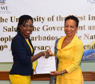 Graduate student Shernell Gittens receiving her award from UWI Cave Hill principal Professor Eudine Barriteau.