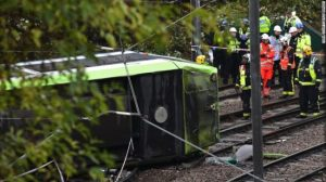 Emergency responders look at the overturned tram in Croydon, south London.