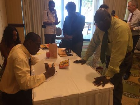 Chief of Protocol Phillip  St Hill autographs one of his new books for a fan.
