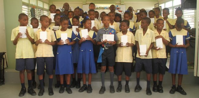 The Class 3 students of A DaCosta Edwards Primary showing off their Samsung Galaxy Tablets donated to them by the Aron and Christina Foundation, as their principal Laureen Hinds (left, at back), Aron Truss (second from left, at back) and Member of Parliament for St Andrew George Payne (right, at back) look on.