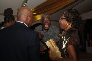 Prime Minister Freundel Stuart sharing a joke with two guests.
