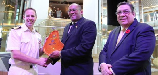Minister of Tourism Richard Sealy presenting the traditional Barbados mahogany plaque to Captain John Westgarth-Pratt, while Chairman of Barbados Port Inc. David Hardinglooks on.