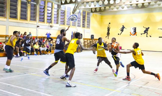 Stephan Ottley  (second right) of Discover 246 Cavaliers gets through Challengers' defence.