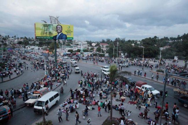 People walk in the street next to an electoral billboard of presidential candidate Jude Celestin of LAPEH (Alternative League for Progress and Emancipation of Haiti) Party ahead of the presidential election, in a street of Port-au-Prince, Haiti, November 17, 2016. REUTERS/Andres Martinez Casares