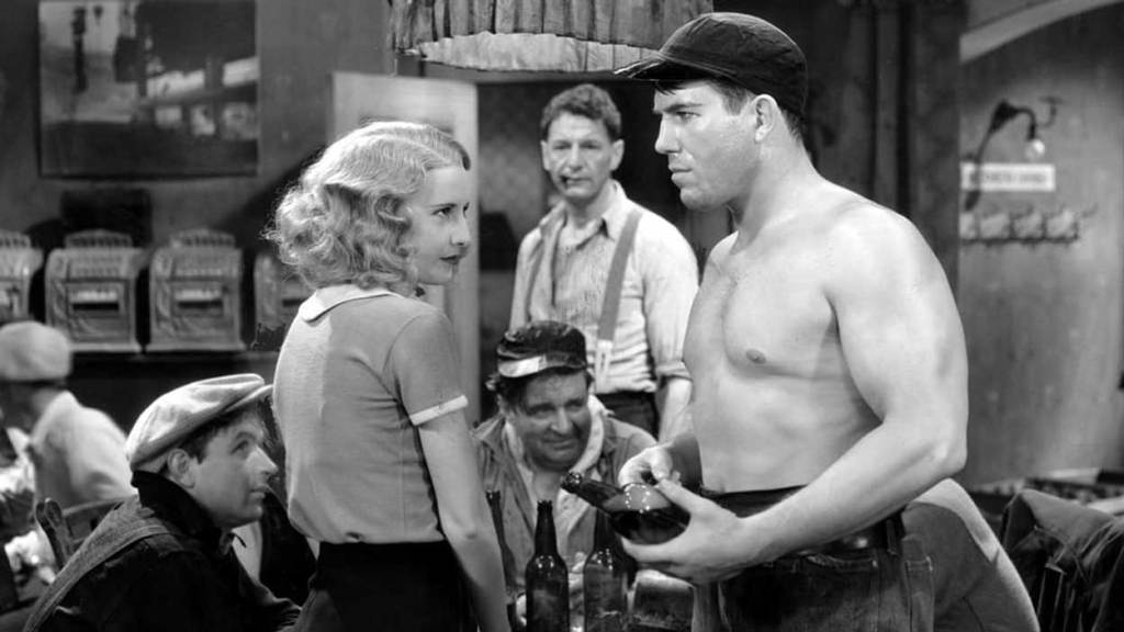 Barbara Stanwyck as Lily Powers in a scene of Stanwyck's top 10 movie Baby Face. Lily Powers fiercely looks at a menacing man trying to take advantage of her, but she is having none of it.