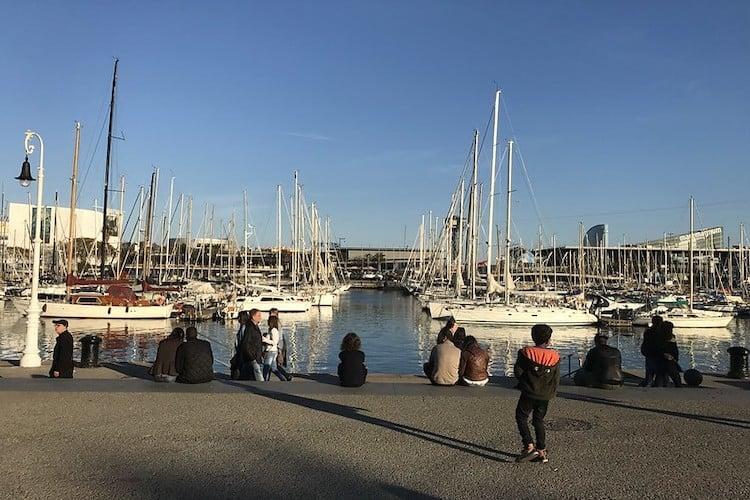 mensen zittend aan de haven port vell
