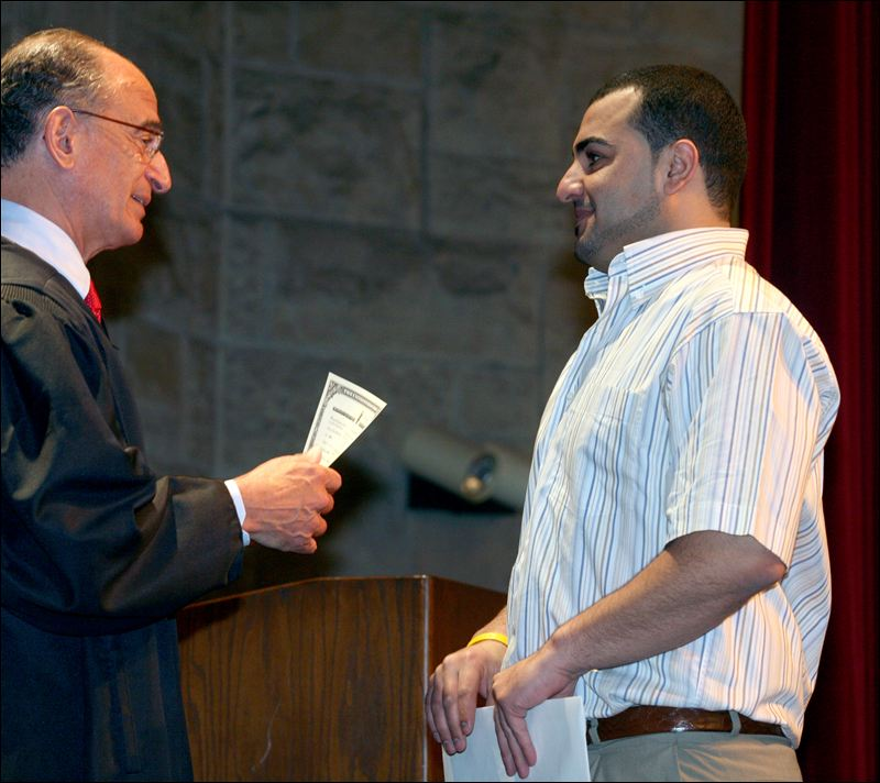 Judge Jack Zouhary congratulates Mohamad Najib Mahmoud at the naturalization ceremony. Mr. Mahmoud is a native of Lebanon. At least 12 other new US citizens at this ceremony were Muslims.
