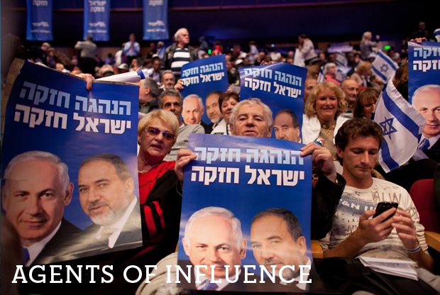 Israelis hold posters of Prime Minister Benjamin Netanyahu and former Foreign Minister Avigdor Lieberman during the launch of the Likud-Beitenu election campaign on December 25, 2012, in Jerusalem.