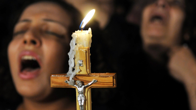 Cristianos egipcios coptos llevan una cruz y oraciones cantar durante una protesta con velas marcando una semana desde que los enfrentamientos sectarios con los soldados y la policía antimotines en una protesta contra el ataque a una iglesia en el sur de Egipto, en la Catedral de Abassaiya en El Cairo