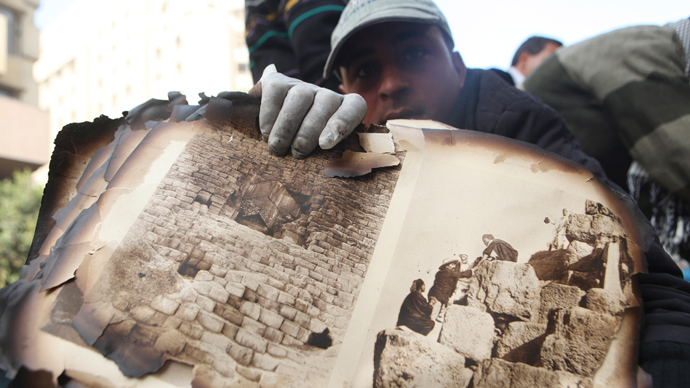 """A worker displays pages from the ancient document """"Le Description de L'Egypt"""" salvaged from the ruins"""