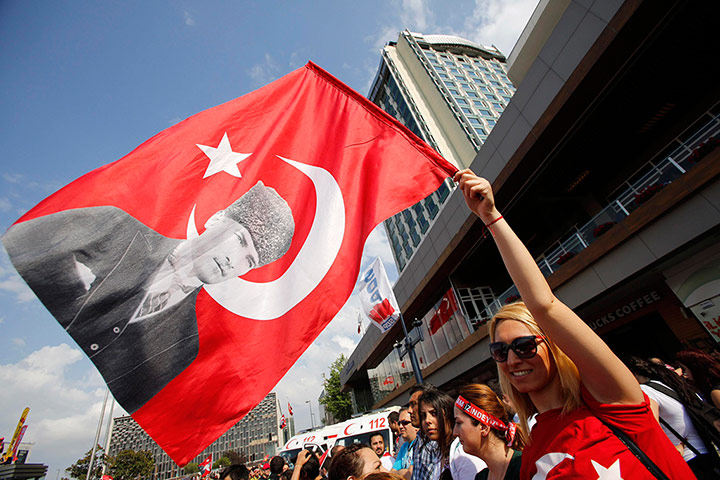 A demonstrator waves a Turkish flag with a portrait of secularist Mustafa Kemal Ataturk during an anti-government protest at Taksim Square in central Istanbul.