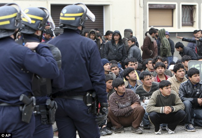 Detained Riot police officers face immigrants in Calais today after the morning raid