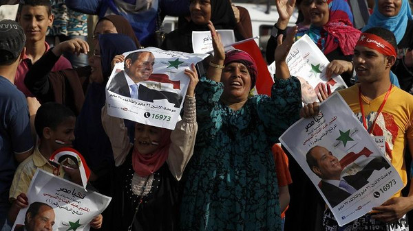 People hold up Sisi posters as they celebrate outside a polling station during the presidential elections in Cairo