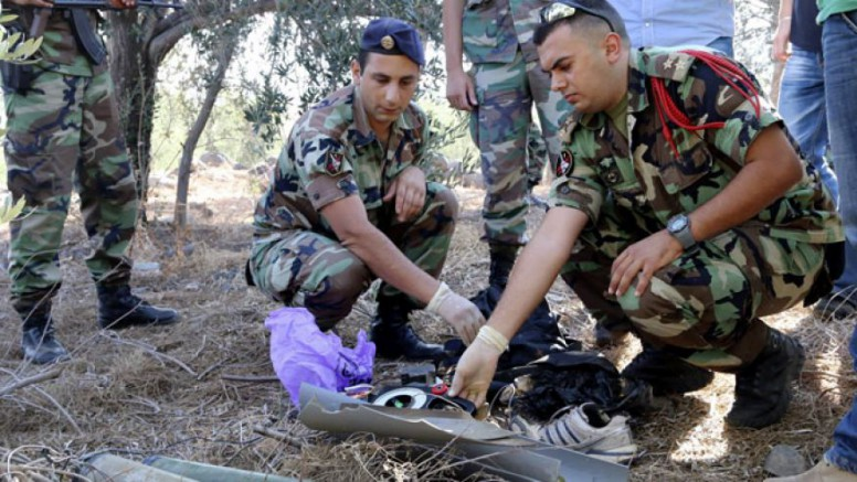 Lebanese army personnel inspect the remains of a shell that was suspected of having been launched from Lebanon to Israel